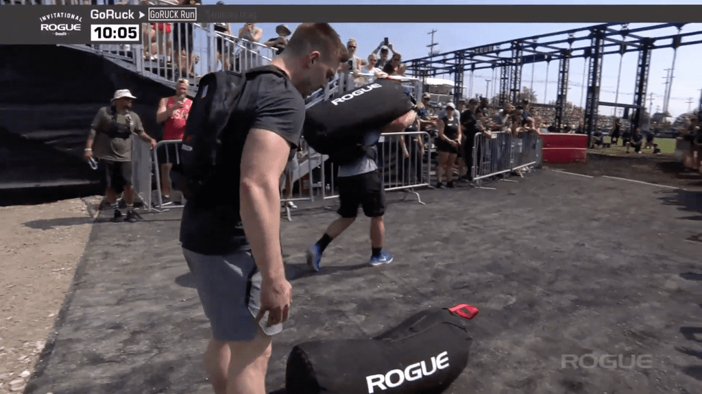 Lukas Hogberg drops his bag and is passed by Mathew Fraser at the GoRuck event of the Rogue Invitational